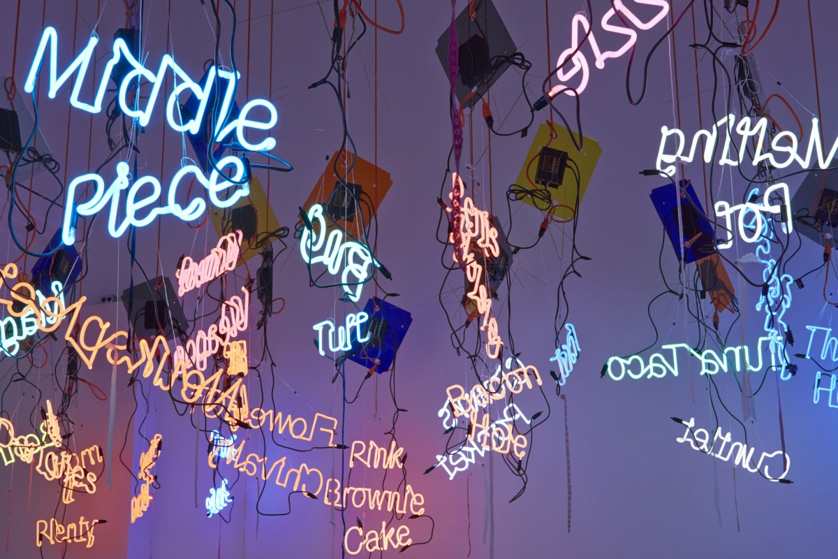 """A photo of hanging neon signs that make up """"My Madinah: In pursuit of my hermitage…"""" by Jason Rhoades"""