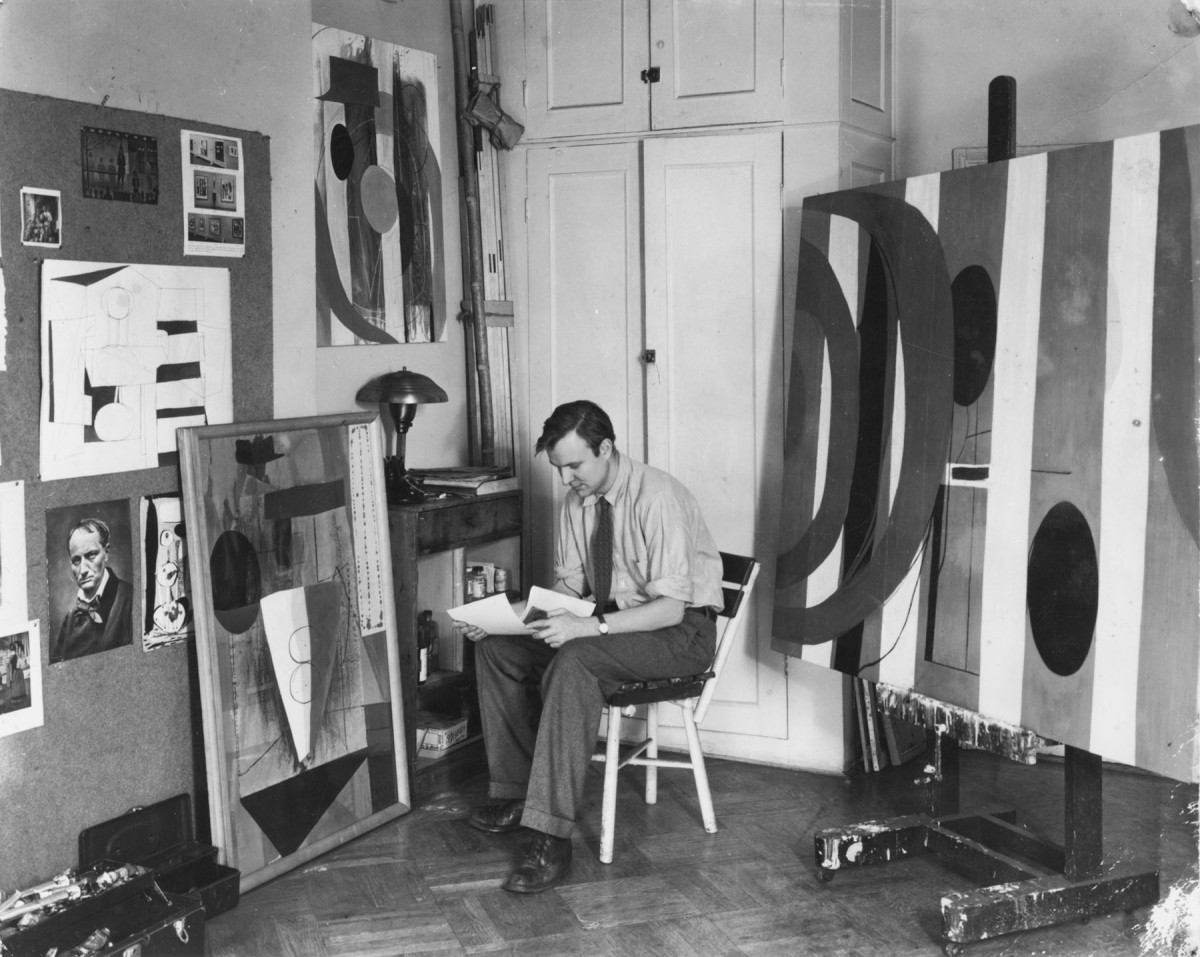 A black-and-white photograph of artist Robert Motherwell in his studio