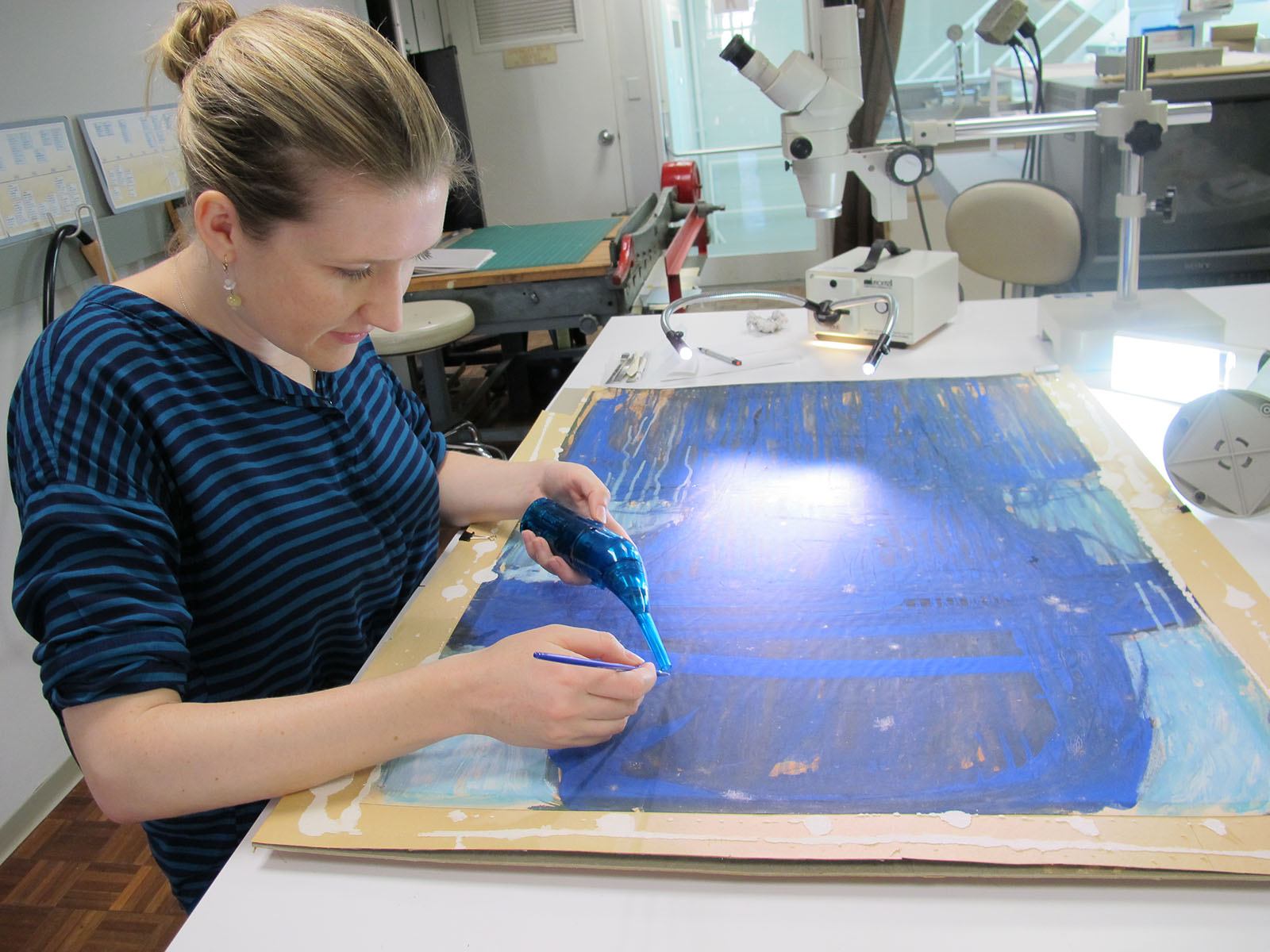 2012-2013 Dedalus Fellow in Modern and Contemporary Conservation, Amy Hughes, using a hand held vacuum and brush to clean the surface of a 1964 painting on paper by abstract expressionist Lester Johnson.