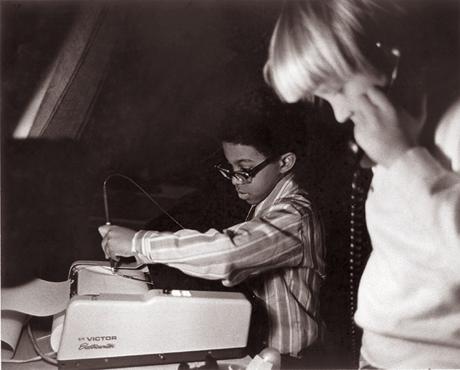 "One of E.A.T.'s Projects Outside Art. A child uses the telephone while a boy writes on the electro writer to communicate with children in another location in the E,A.T. ""Children and Communications"", 1971. Photo Shunk-Kender"