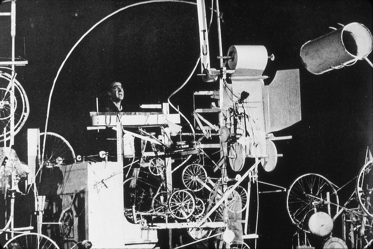 Jean Tinguely stands behind his self-destroying drawing machine, designed and constructed in collaboration with engineers Billy Klüver and Harold Hodges, at the beginning of its operation. The event, titled Homage to New York, took place March 17, 1960, in the Garden of the Museum of Modern Art in New York. Photo David Gahr. Estate of David Gahr.