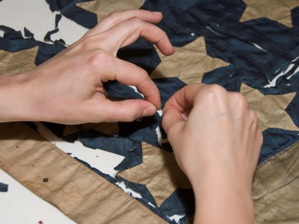 A photograph of two hands repairing a shattered flag
